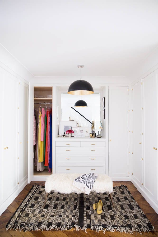 White dressing room with natural wood floor and Moroccan rug.