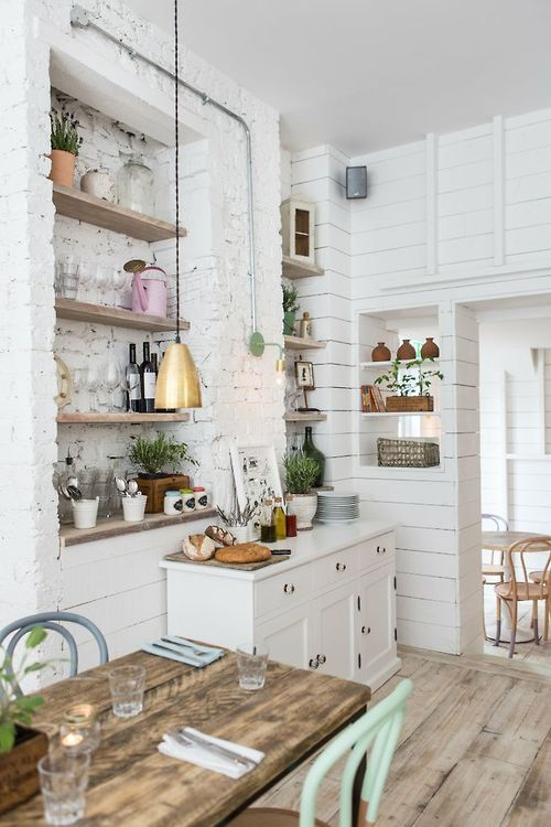 Hally's, a California-inspired cafe in London, creates a homey feel with shiplap siding, exposed/painted brick, warm woods and painted furniture.