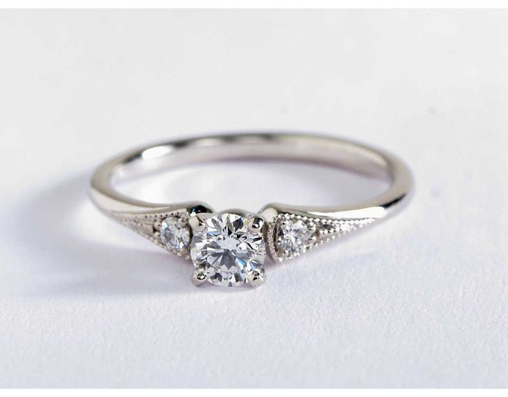 Vintage-inspired, this delicate 14k white gold engagement ring features 2 pavé-set round diamonds surrounded by a milgrain edge.