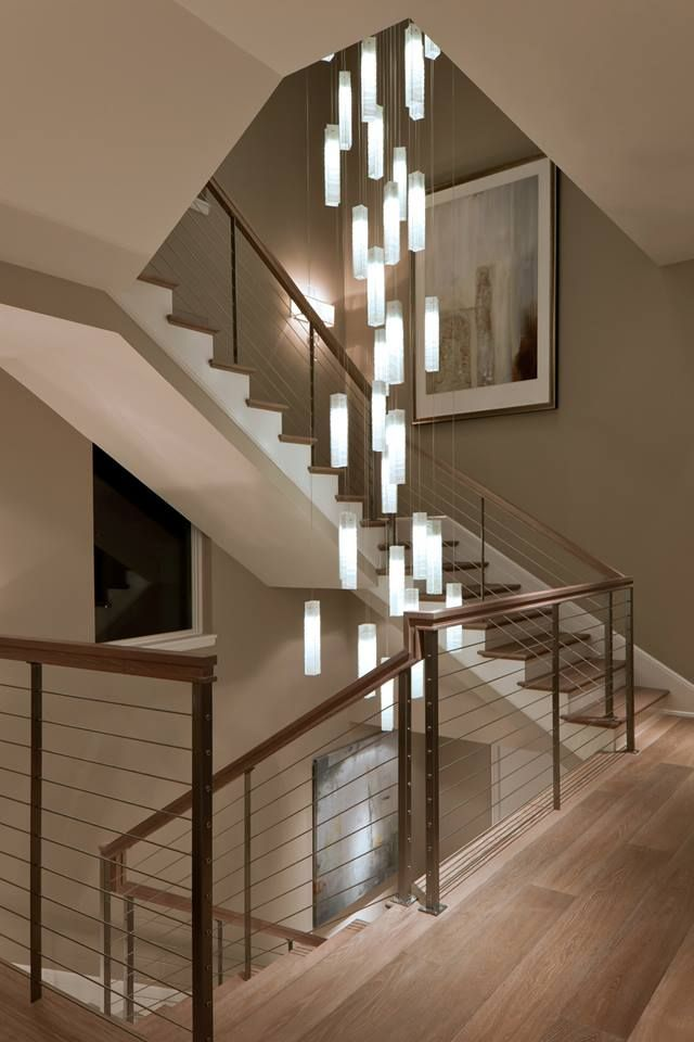 White Candles Pendant Lighting Suspended Into A Beautiful Spiral Stairwell