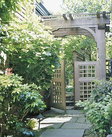 Asian-Inspired Entry - This arbor blends a subtle mix of Asian-inspired touches but has no dominant stylistic theme. Large timbers make up the frame, square grid panels fill in the gates, and the curved knee braces create a cloud-lift effect where they meet the beams overhead.