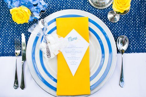 Blue and yellow 'Let's go fly a kite' mary poppins inspired wedding table place setting. Floral Design & Styling by Boutique Blooms. Photo by Anneli Marinovich Photography. Stationary by Eagle Eyed Bride. Blue and yellow wedding flowers. Engraved teaspoons by the Cutlery Commision Vintage silver by Idyllic Day hire.