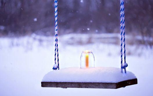 Обои Свеча в высоком стеклянном подсвечнике стоит на заснеженных качелях