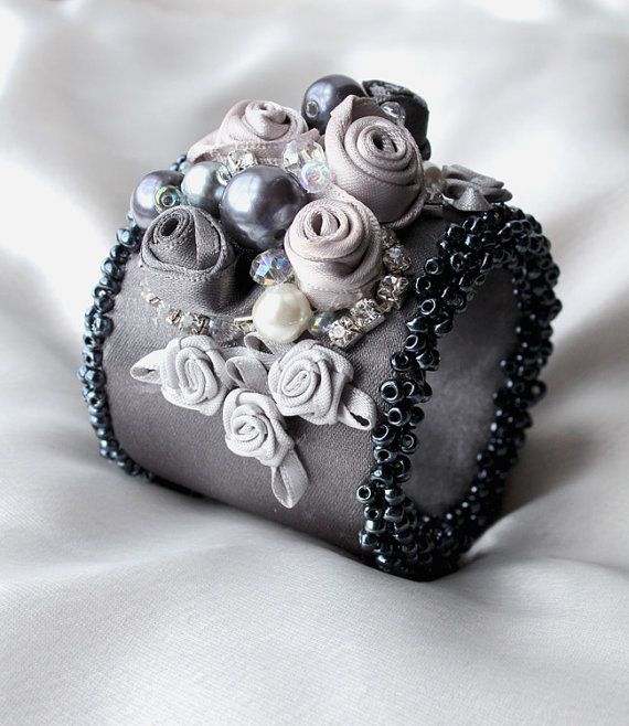 Sombre et dramatique! Ce bracelet manchette est fait avec ruban de satin en étain et recouvert de strass, perles, cristaux et roses de ruban à la main. Les bords ont été à la main agrémentée de perles de rocaille en étain pour créer afrilly bord qui lui donne un look victorien ou Vintage. Bien qu'il soit brillant et féminin en même temps. Il y a un bouton de fermeture. Le brassard est assez souple et convient à un tour de poignet de petite et moyenne. Cet article sera emballé pour vous…