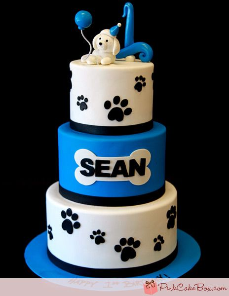 This first birthday cake is centered around the dog on the top tier who is decked out in a turquoise party hat and holding a balloon. The cake is covered i