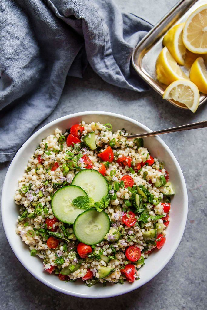 This Israeli Couscous Tabbouleh Salad recipe combines pearl couscous with tomatoes, cucumber, fresh herbs and a light citrus dressing. It's a perfect make-ahead salad recipe!   platingsandpairings.com