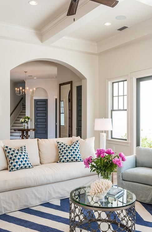 Cottage living room features a coffered ceiling accented with a fan over tan slipcovered skirted ...