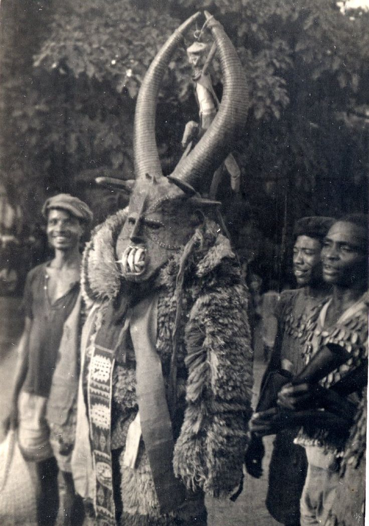 North Nigeria, adult male [?] wearing masquerade costume. Costume covered with fluffy or furry material, patterned panels at front. Mask has long horns and sharp teeth. Small group of adult males accompanying masquerader, male at right possibly playing percussion-instruments. Outdoor setting. Medium: Gelatin silver print.