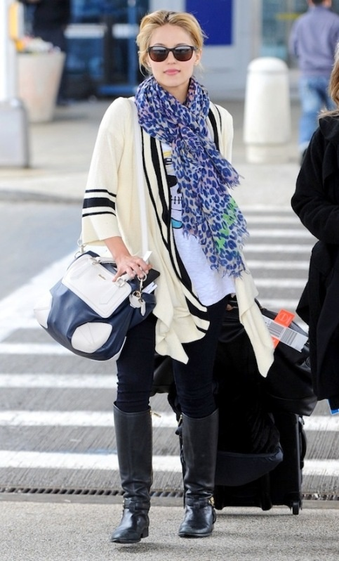 Tall boots, loose sweater, pop of color scarf. ##traveloutfit or comfy #airplaneoutfit