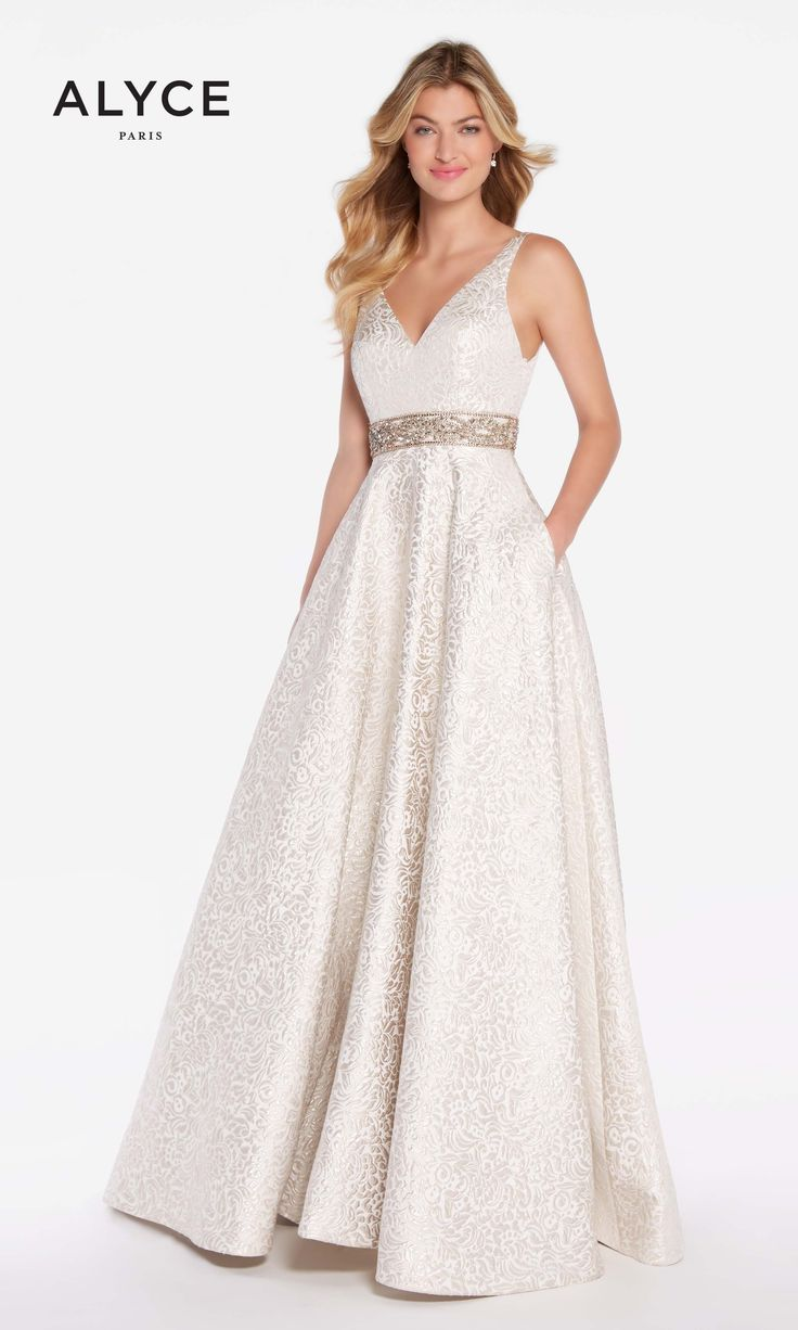 Champagne Dreams in Alyce 60121. This princess gown is a delicate creamy brocade fabric with swirled details. The golden belt defines the waistline below the deep V-cut front and back of the dress. The soft color and detail of this dress make it irresistable for your next prom, pageant, or formal event.