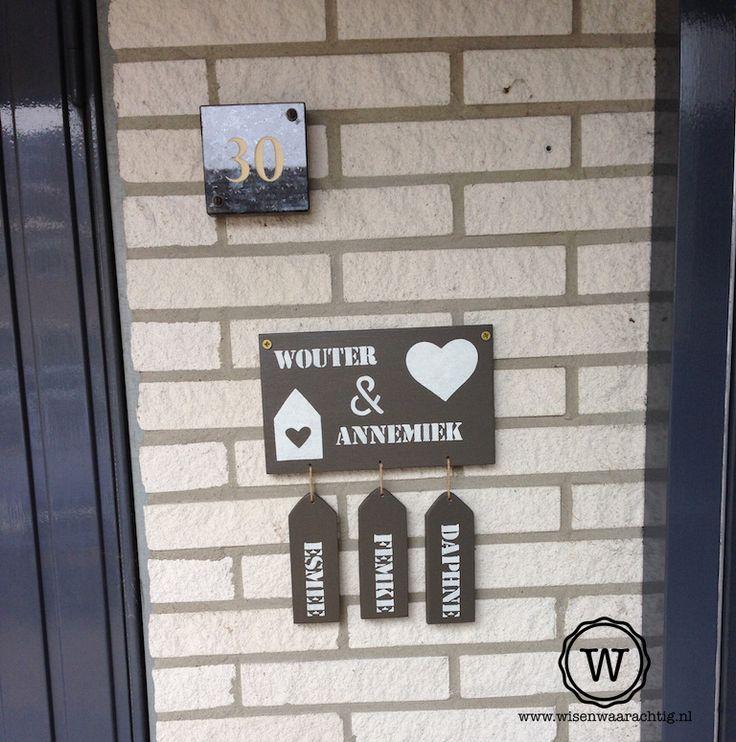 Naambord bij de voordeur met drie losse labels voor de namen van de kinderen.