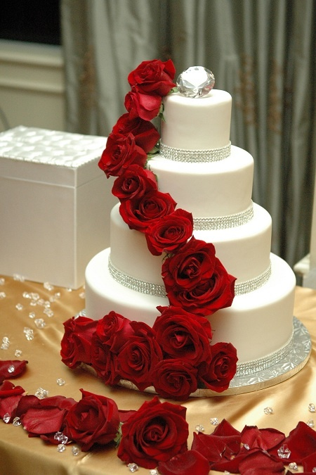 Cascading  red roses on a fantastic wedding cake. We are in love with the diamond wedding cake topper. Repin by Inweddingdress.com #weddingcakes