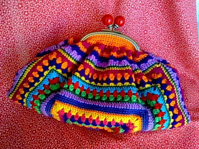 Granny Square Chic Clutch (I'm thinkin, a granny square, gathered and then attached to a frame, perhaps)