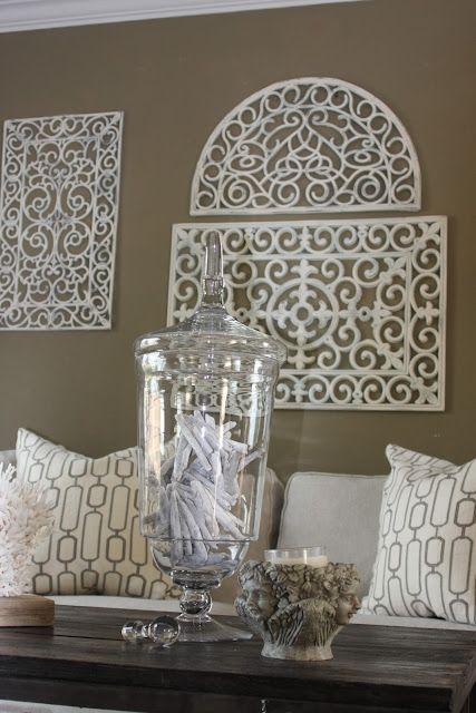 a living room fit for a modern-day House Greyjoy: iron-wrought wall decor, wooden tables, and nautical and cement accents DIY iron-wrought wall decor: Rubber Door Mat, spray paint