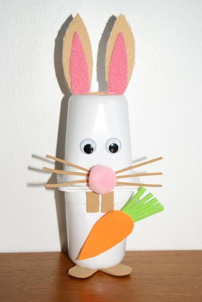 Petit lapin blanc avec des pots de yaourts