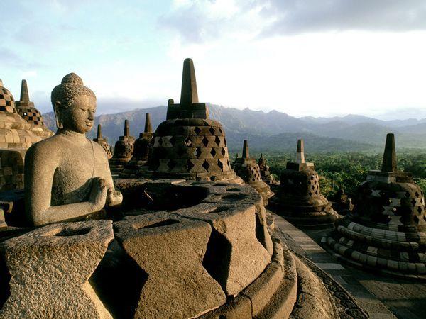 Stupas at Borobudur, the world's largest Buddhist temple, overlook Java's jungles. indonesia