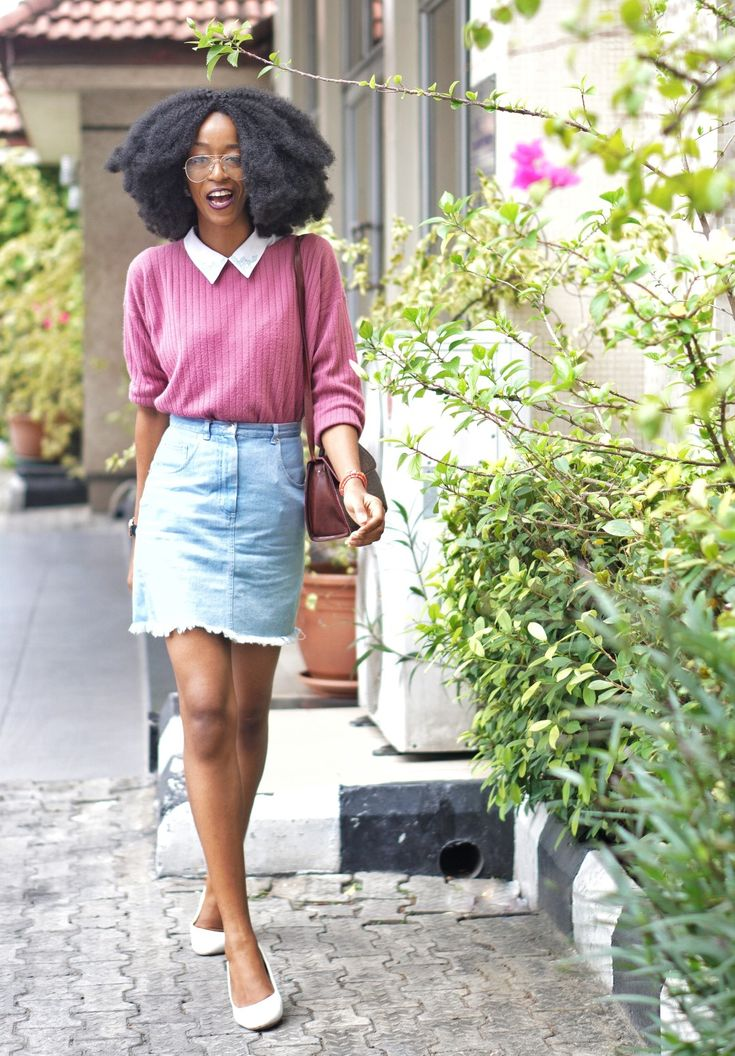 nigerian fashion blogger Cassie daves sporting a big afro, denim mini skirt, and white court shoes