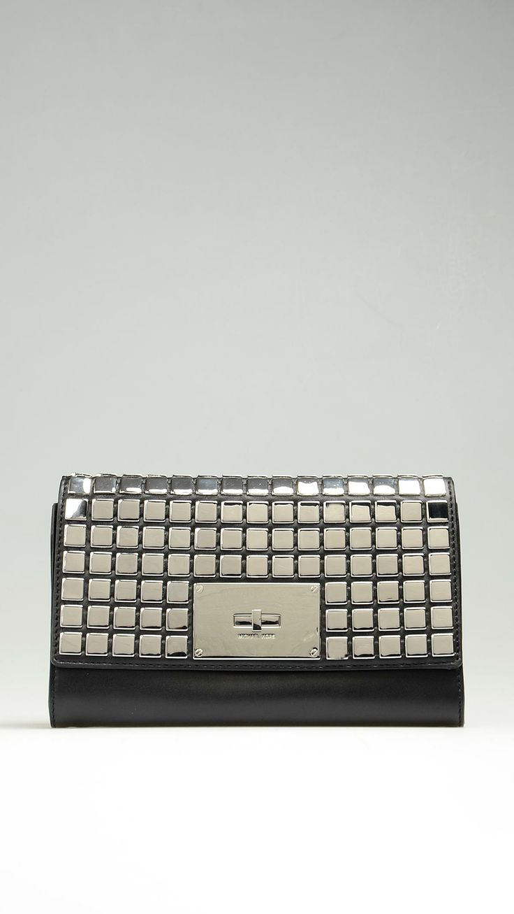 Black calfskin with allover silver tiles. Front flap close with logo-engraved turn-lock. 9.8 X 5.9 X 1.2 inch. 25 X 15 X 3 cm.
