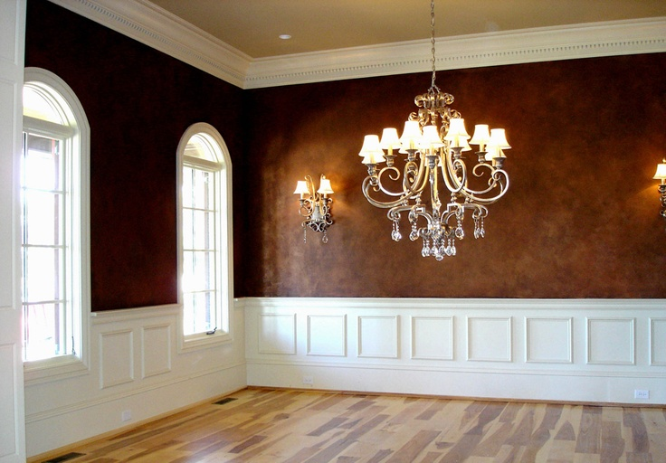 Copper and chocolate glazed walls, white chair railing, crown molding, fabulous windows and light fixture.