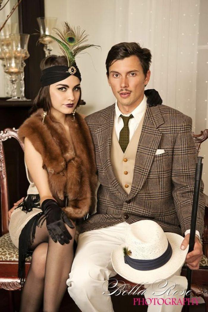 Partnerkostüm inspiriert von dem Film Der große Gatsby, Paarkostüm im Gatsby-Stil, Frau mit schwarzer Haarband mit einem Feder, Schal aus Tierfell und schwarze Handschuhe, Mann mit kariertem Sakko, beige Weste und weißem Hemd mit grüner Krawatte, weiße Hose mit Falten und weißer Hut mit schwarzem Band