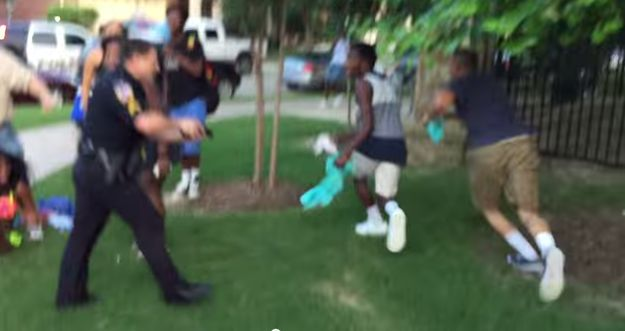 """A police officer in McKinney, Texas, has been suspended from duties after being filmed aggressively handcuffing, and then pulling a weapon on, a group of black teens following an """"incident"""" at a local pool party on Friday night. 