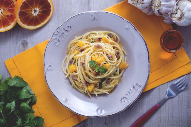 Gli spaghetti all'arancia con acciughe, così particolari e gustosi, sono il primo piatto ideale per sorprendere parenti e amici con originalità.