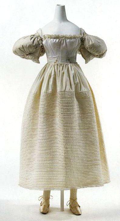 Корсет, сорочка-шемиз, нижняя юбка и подушечки-подкладки под рукава. 1830-е. Белый корсет из простеганного шнуром хлопчатобумажного атласа с вышивкой, сорочка-шемиз из белого хлопка, льняная нижняя юбка, подрукавные подушечки из вощеного ситца, набитые пухом.