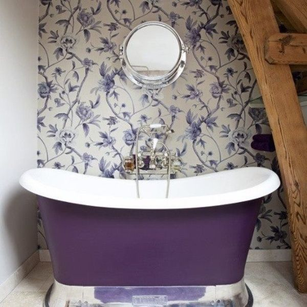 A Purple Soaking Tub With Floral Purple Wallpaper On The Wall Behind It
