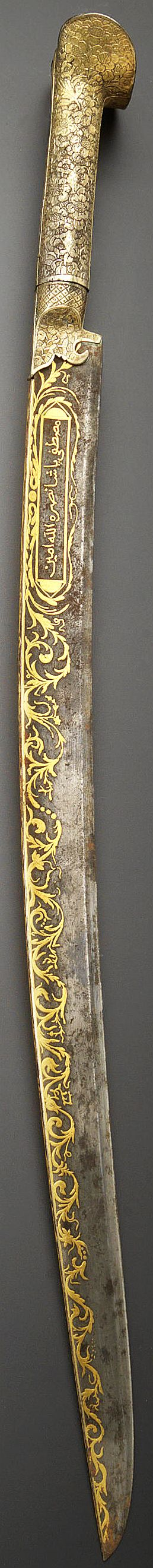 Ottoman yataghan / yatagan, circa 1800, slightly curving blade and tapering point, the spine and sides decorated with bands of gold overlay consisting of undulating leafy and floral vines, one side with an inscription-filled cartouche,  76 cm. long. The inscriptions comprise: mustapha pasha nasarahu allal amin, 'Mustapha Pasha may Gold help him, Amen!'.