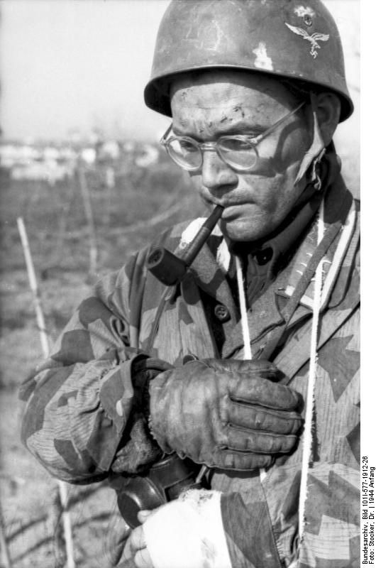 "German paratrooper smoking pipe. Apparently pipe smoking was very popular among German paratroopers, maybe the pipe, in that context, was seen as a symbol of ""relax"" and self-confidency for propaganda purposes. Monte Cassino, Italy, January 1944 ."