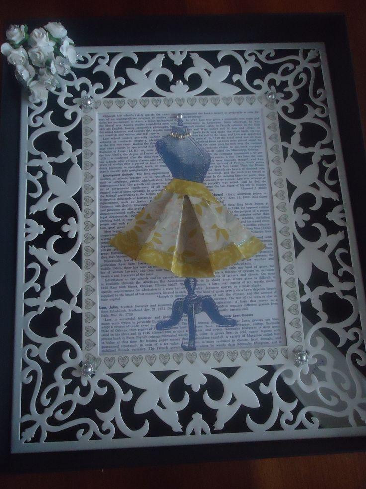 kleding gevouwen en versierd met glitterlijm, kraaltjes geregen en lijstje van Ikea versierd met maskingtape en bloemetjes van papier. Glitterkralen geplakt. De bladzij met de paspop is op pinterest te vinden