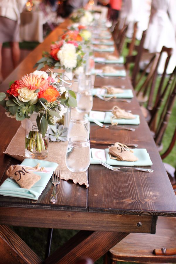 Wedding guest table setup with orange and coral florals, and burlap and mint accents