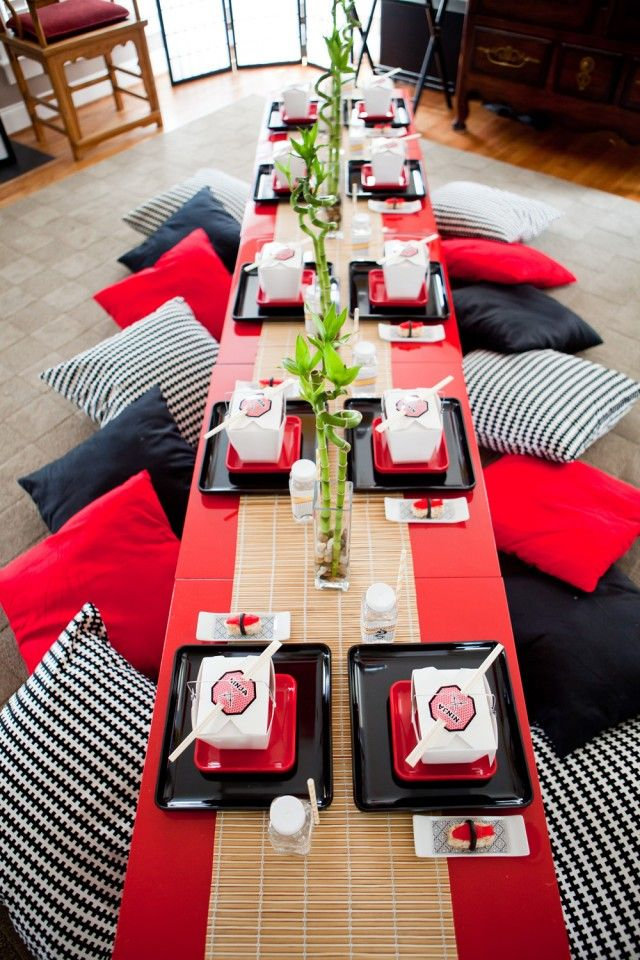 """Super Hero Ninja Party - Each place setting had a black/red square plate with Chinese take out container holding lunch - chopsticks were placed on top. A small ceramic white dish was beside the plates. It held a single piece of candy sushi on patterned paper lining. DIY bamboo runner (dollar store placemats sewn together) """"Lucky Bamboo Shoot"""" centerpieces ran down the center of the table in vases with rocks. Ninjas kneeled at red IKEA lacquered tables on floor pillows!"""