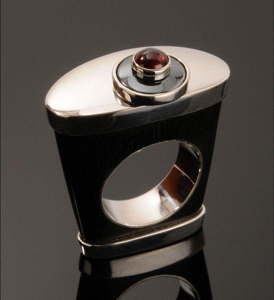 Piękny pierścionek wykonany ze srebra próby 925, hebanu, hematytu oraz granatu. Nowoczesna forma idealnie pasuje do codziennej stylizacji. To propozycja na zaskakujący prezent.