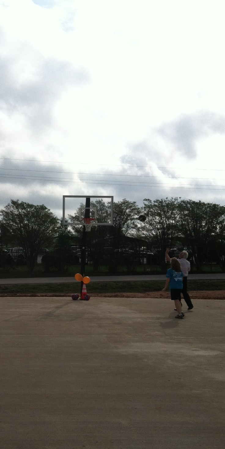 Mayor Mac Woodward shoots hoops at the new Kate Barr Ross Park basketball court.