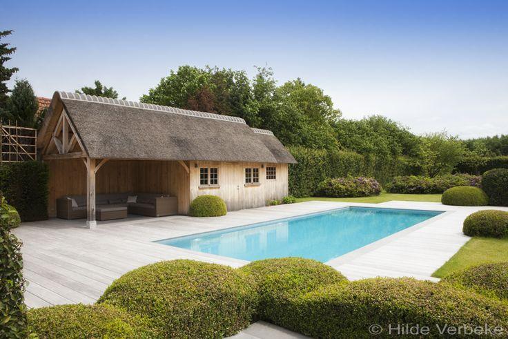Dit betonnen luxe buitenzwembad bekleed met lichtgrijze mozaïek is een skimmer zwembad aangelegd door Azur Pools.De landelijke poolhouse maakt het plaatje af