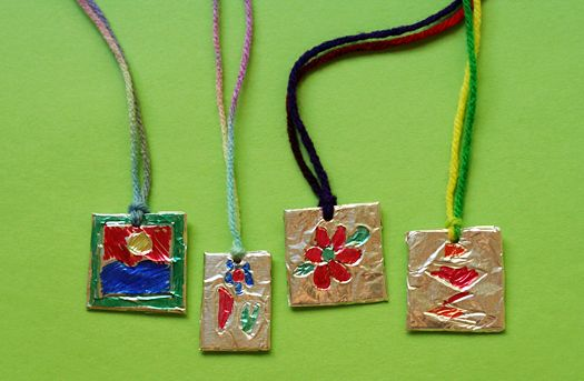 Easy embossed foil pendants for kids to make. Materials: craft foam sheets aluminum foil clear tape dull pencil or medium ball point pen colored Sharpies hole punch yarn or ribbon Craft foam sheets and foil are easy to cut, so big kids will probably be able to do all the steps for these pendants on their own. Yay for low-maintenance craft projects!