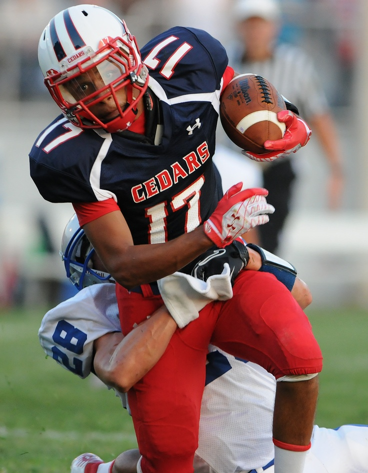 Lebanon's Taj Cintron is wrapped up by Cedar Crest's Damon Edwards during the first half of the 41st annual Lebanon Cedar Bowl at Alumni Stadium on August 31, 2012. LEBANON DAILY NEWS - JEREMY LONG