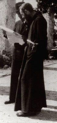 Padre Pio intento alla lettura di un giornale, insieme ad Emanuele Brunatto, uno dei suoi primi figli spirituali, morto in circostanze misteriose nel 1965, al tempo della seconda persecuzione del Frate