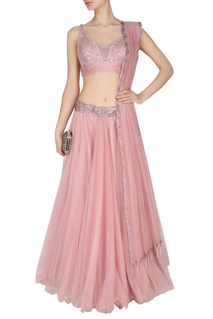 This set features an onion pink layered flared skirt, set in tulle base. It is appliqued with pink thread work embroidery and crystal sequins in paisley motifs