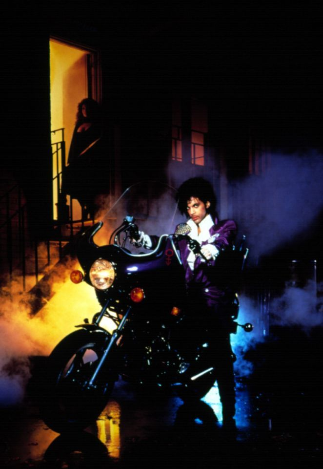 """The poster image for the 1984 movie """"Purple Rain,"""" featuring Prince in arguably his most memorable look. But besides the music, this image of Prince perched on a motorcycle in all his purple glory will remain etched in our memories. The look, which included a pair of pants with an asymmetric fly, a ruffled white shirt and a long purple coat with chain mail on one shoulder, was created by Louis Well and Terry Vaughn, who also designed costumes for Earth, Wind and Fire. Photo: Getty."""