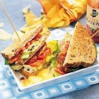 American BLT sandwich met bacon, grof volkorenbrood met zonnepit, mayonaise, botersla, trostomaat, tomatenketchup en chips naturel