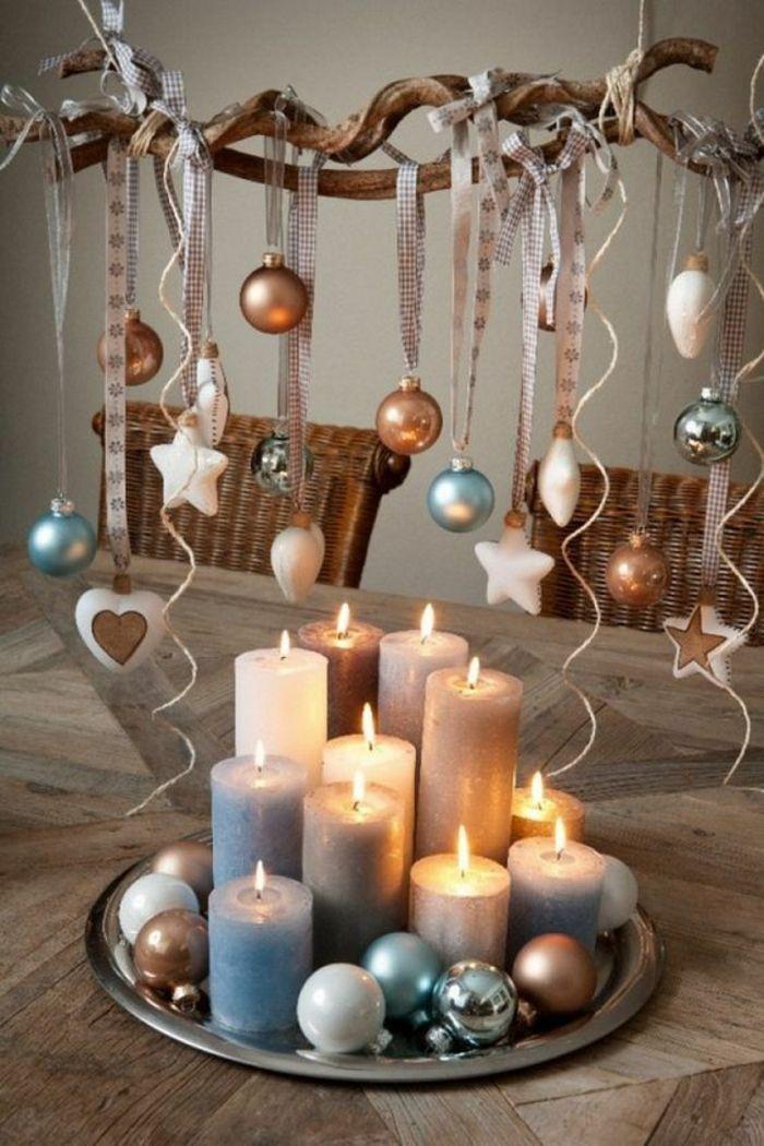 Weihnachtsdekoration, Weihnachtsschmuck, mit elf breiten und kleinen Kerzen und bunten Tannenkugeln, alle auf einem silbernen runden Metalltablett, Zweig mit Kugeln und Sternen mit Bändern aufgehängt Fliesen