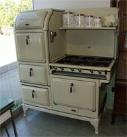"""This links to a wonderful site for antique and vintage stoves! From the 1930's, this Magic Chef features 6 burners, a double oven, warming oven, storage drawer, and shelf. It is cream colored with black trim, and come with a custom vent hood. It measures 53"""" wide x 64"""" tall."""