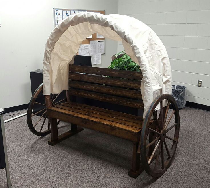 """""""Pioneer Day""""-Covered wagon/bench for schools. Pool noodles support the canopy. Staple or sew sheets around the noodles. Add wagon wheels, and it creates a nice photo booth. If your pool noodles are bright colors, tape brown construction paper around the part that's showing."""