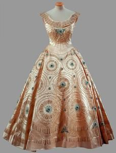Cream crinoline gown with blue embroidery - Norman Hartnell  A fine example of Hartnell's crinoline-inspired evening gowns with magnificent jewelled embroideries. Worn by Queen Elizabeth II during the Tour of Canada and the United States of America, October 1957.