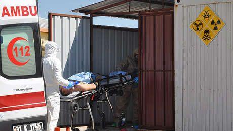 Un hombre sirio es trasladado por médicos turcos que visten trajes de protección química a un hospital de la ciudad de Reyhanli (Turquía).
