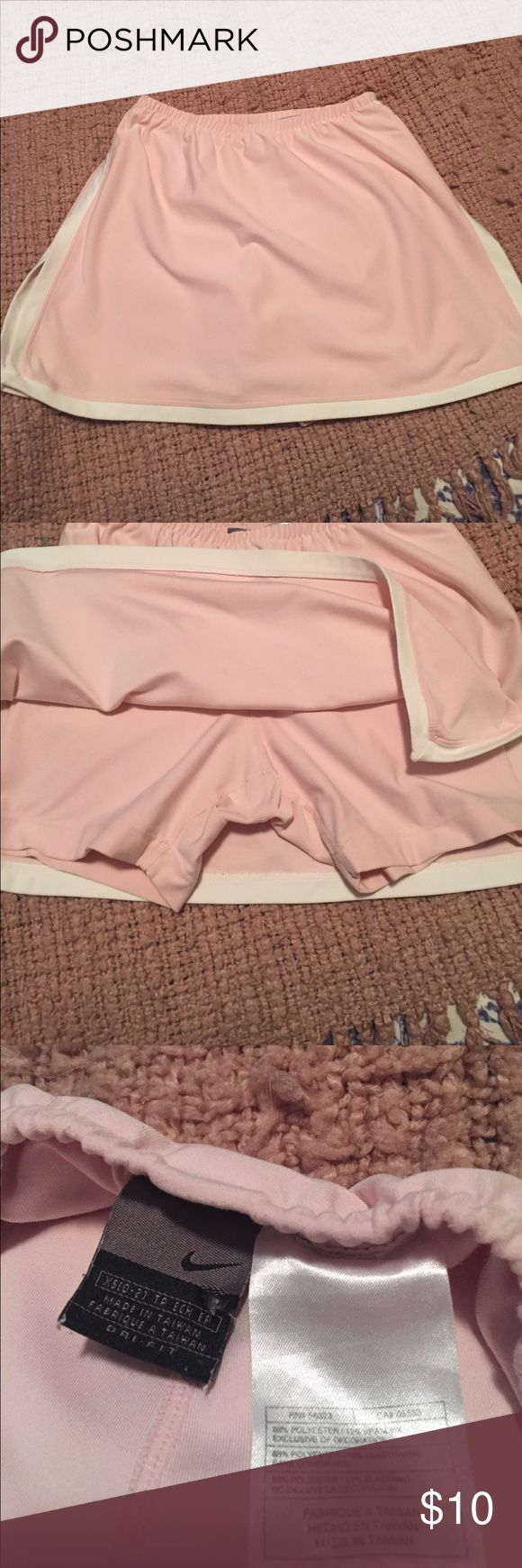 Nike skort Nike skirt for all your activities. Great for tennis, golf, walking and running.  Good condition with no stains or tears.  Open to offers.  Color is a light pink and white. Nike Skirts