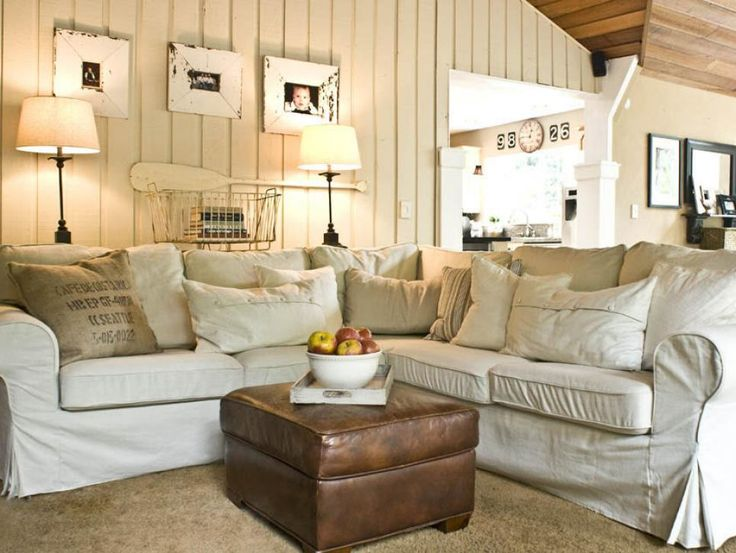 This cottage-style living room features a sectional with slipcovers, wood paneling, burlap pillows and a vintage leather ottoman. Coastal accents like a mounted oar and shabby chic picture frames complete the room.