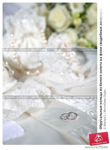 Обручальные кольца из белого золота на фоне свадебных аксессуаров © Mariya L / Фотобанк Лори